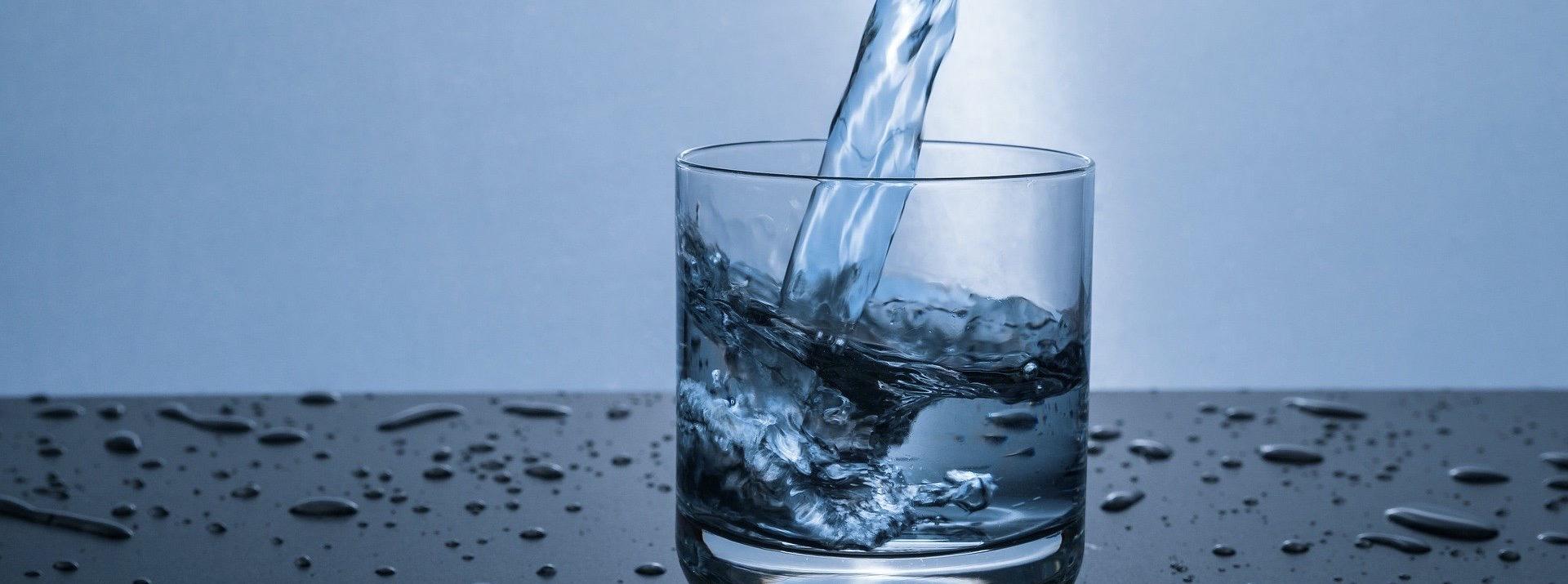 Wasser wird in Glas eingeschenkt